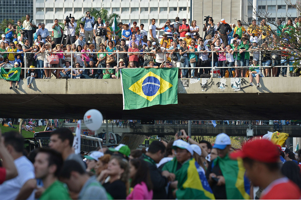 . People wait across the city for Pope Francis to pass in an open-top jeep after his arrival in Rio de Janeiro on July 22, 2013.    AFP PHOTO / GABRIEL BOUYS/AFP/Getty Images