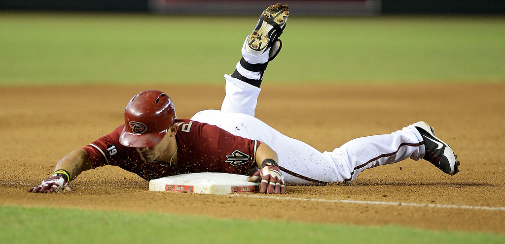 . Outfielder Gerardo Parra #8 of the Arizona Diamondbacks safely slides into third base after hitting a triple to deep center against the Colorado Rockies in the fourth inning at Chase Field on September 15, 2013 in Phoenix, Arizona.  (Photo by Jennifer Stewart/Getty Images)