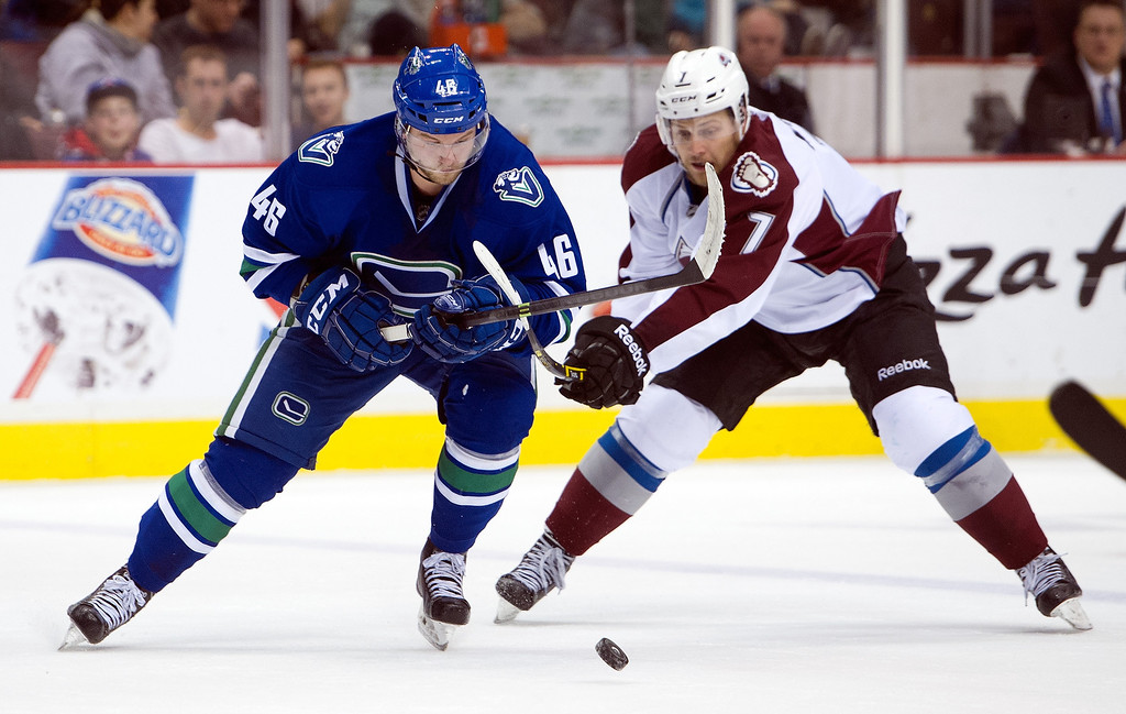 . Nicklas Jensen #46 of the Vancouver Canucks tries to fight off the check of John Mitchell #7 of the Colorado Avalanche while skating with the puck during the second period in NHL action on April 10, 2014 at Rogers Arena in Vancouver, British Columbia, Canada.  (Photo by Rich Lam/Getty Images)