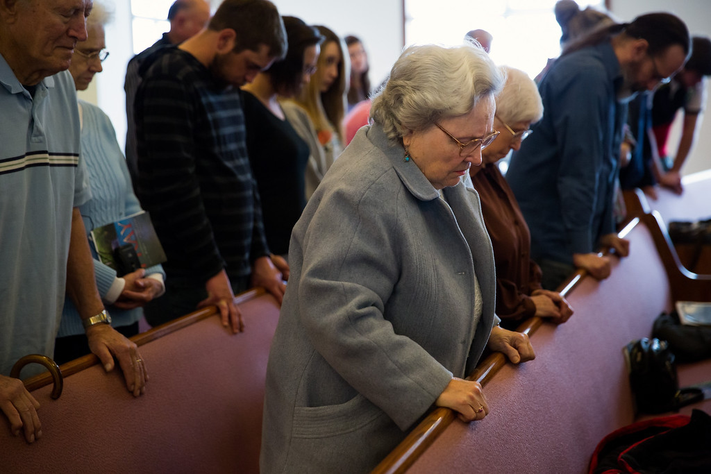 . Rose Fagerberg, center, bows her head in prayer during Sunday church service at the Glad Tidings Assembly of God, in Darrington, on Sunday, March 30, 2014. (AP Photo/The Seattle Times, Marcus Yam)