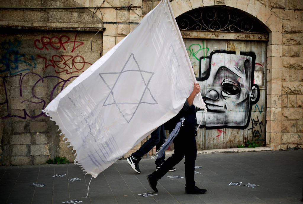 . An Israeli man holds a prayer shawl with the Star of David on it as he walks during a rally in Jerusalem, Sunday, March 2, 2014. Israeli police closed the main highway into Jerusalem and the city\'s central roads Sunday ahead of a mass rally by ultra-Orthodox Jews protesting government plans to draft them into the army. (AP Photo/Ariel Schalit)
