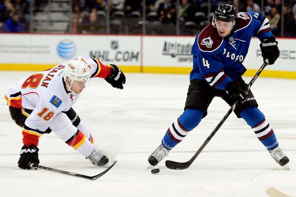 . Tyson Barrie (4) of the Colorado Avalanche keeps the puck away from the defense of Matt Stajan (18) of the Calgary Flames during the first period.   (Photo by AAron Ontiveroz/The Denver Post)