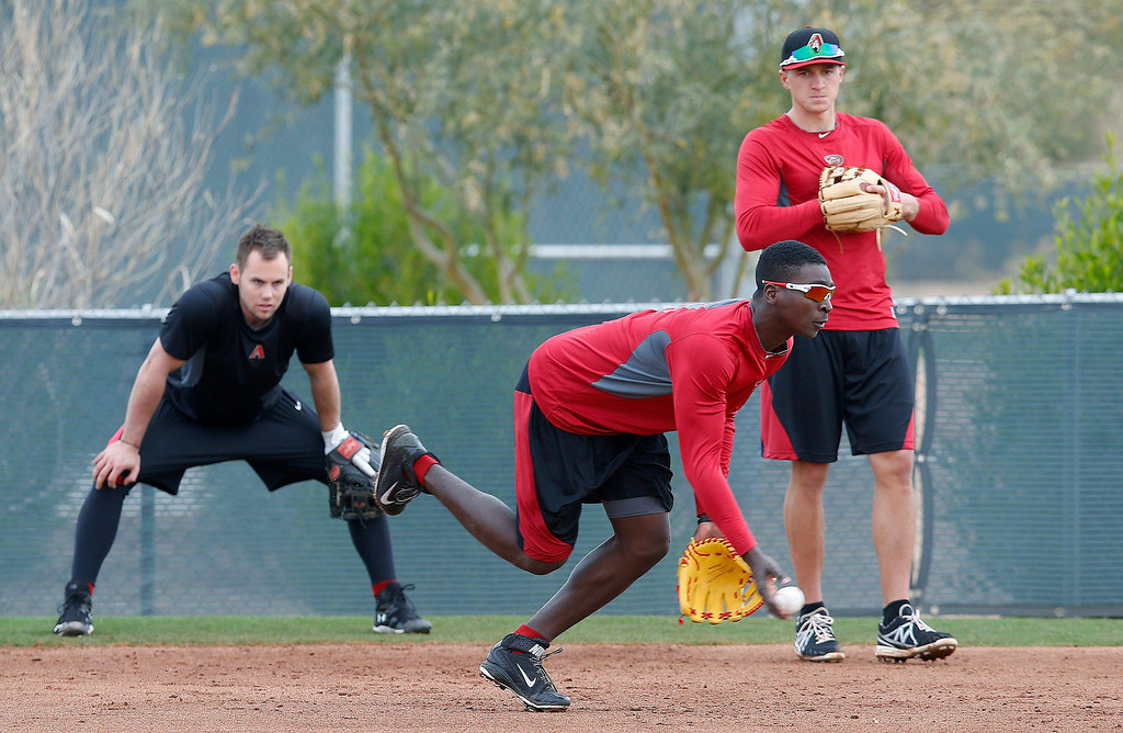 . Arizona Diamondbacks\' Didi Gregorius, front, tosses the ball to second base, as teammates Chris Owings, left, and Nick Ahmed watch as the players have an informal practice a day prior to pitchers and catchers practicing for the first day of baseball spring training, at the Diamondbacks\' facility Thursday, Feb. 6, 2014, in Scottsdale, Ariz. (AP Photo/Ross D. Franklin)