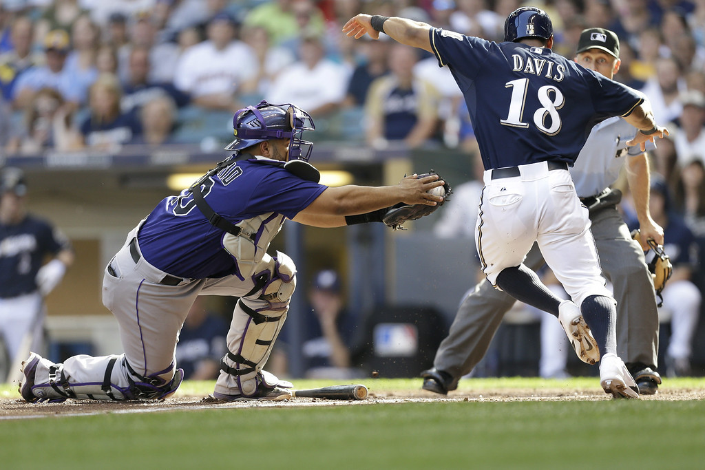 . MILWAUKEE, WI - JUNE 28: Khris Davis #18 of the Milwaukee Brewers tags out Wilin Rosario #20 of the Colorado Rockies as he attempt to get to home plate in the bottom of the sixth inning at Miller Park on June 28, 2014 in Milwaukee, Wisconsin. (Photo by Mike McGinnis/Getty Images)