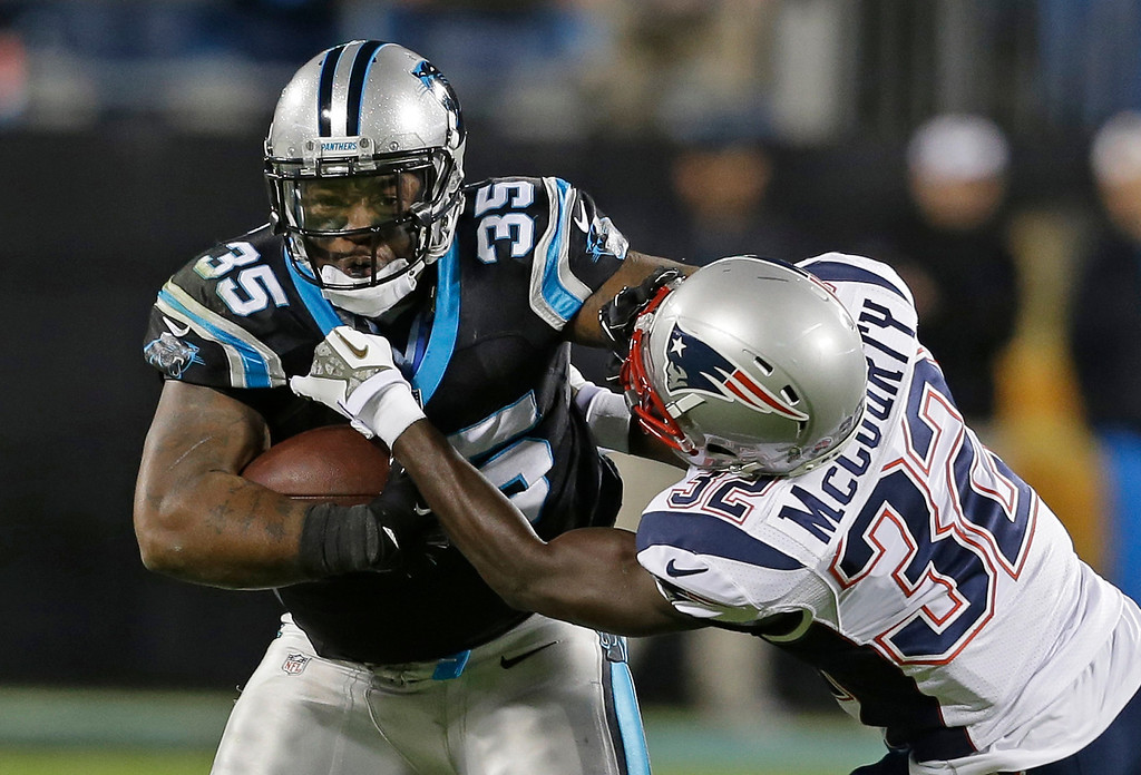 . Carolina Panthers\' Mike Tolbert (35) is tackled by New England Patriots\' Devin McCourty (32) during the second half of an NFL football game in Charlotte, N.C., Monday, Nov. 18, 2013. (AP Photo/Gerry Broome)
