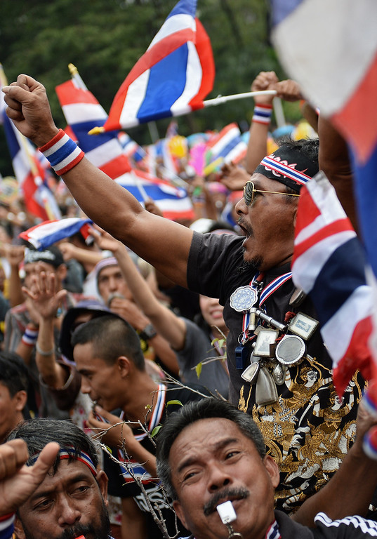 . Thai opposition protesters react to a leader\'s speech on a stage set up at the occupied Finance Ministry in Bangkok on November 26, 2013.   AFP PHOTO/Christophe  ARCHAMBAULT/AFP/Getty Images