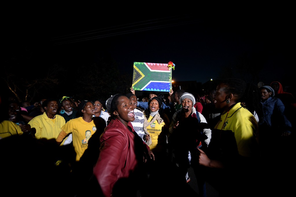 . People sing and dance in front of the Medi Clinic Heart hospital in Pretoria on June 27, 2013. Emotional crowds gathered outside the hospital where Nelson Mandela showed tentative signs of improvement on June 27. FILIPPO MONTEFORTE/AFP/Getty Images