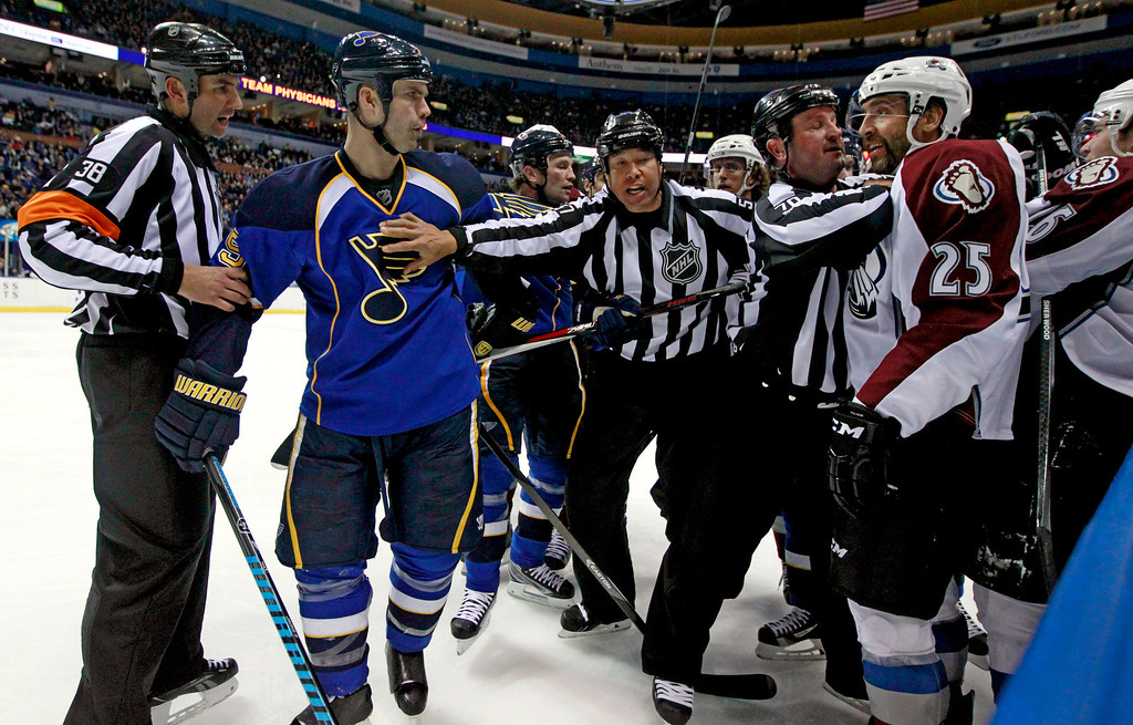 . Officials try to keep St. Louis Blues\' Barret Jackman and Colorado Avalanche\'s Maxime Talbot (25) apart during the third period of an NHL hockey game Thursday, Nov. 14, 2013, in St. Louis. The Blues won 7-3. (AP Photo/Jeff Roberson)
