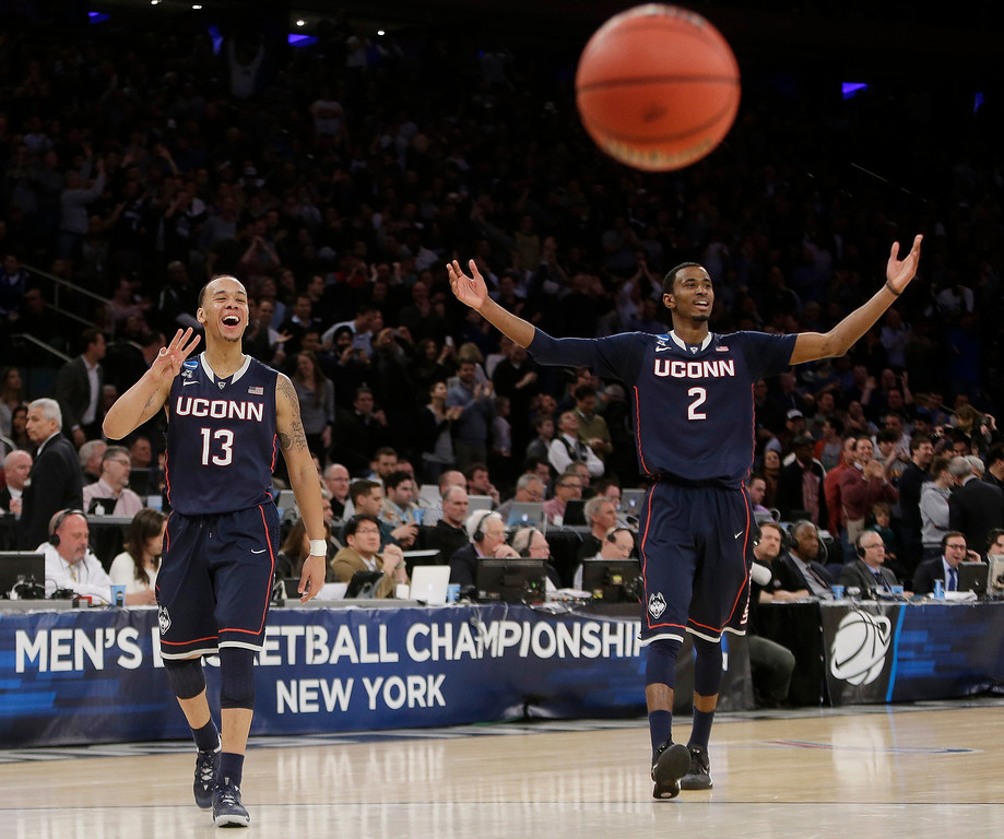 . Connecticut\'s Shabazz Napier (13) and DeAndre Daniels (2) gesture to their teammates during the second half of a regional final against Michigan State in the NCAA college basketball tournament, Sunday, March 30, 2014, in New York. Connecticut won 60-54. (AP Photo/Frank Franklin II)