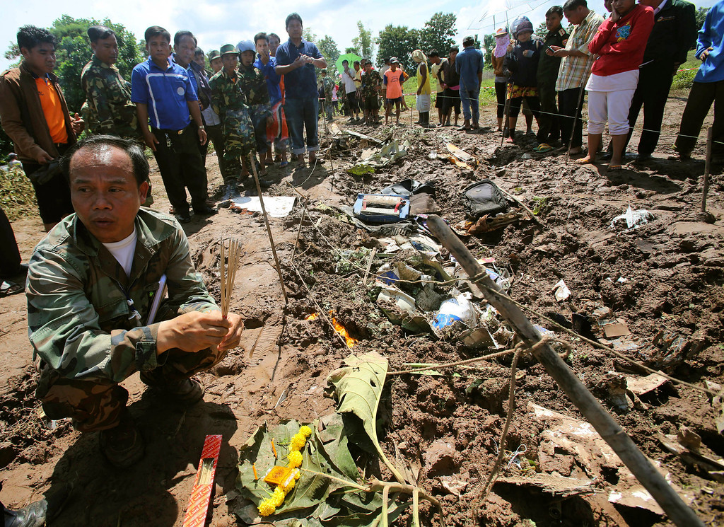 . A Lao soldier prepares to place incense sticks into the ground beside the wreckage left by a Lao Airlines turboprop plane as he pays his respects to the victims of Wednesday\'s ill-fated flight, in Pakse in Laos, Thursday, Oct. 17, 2013.  (AP Photo/Sakchai Lalit)