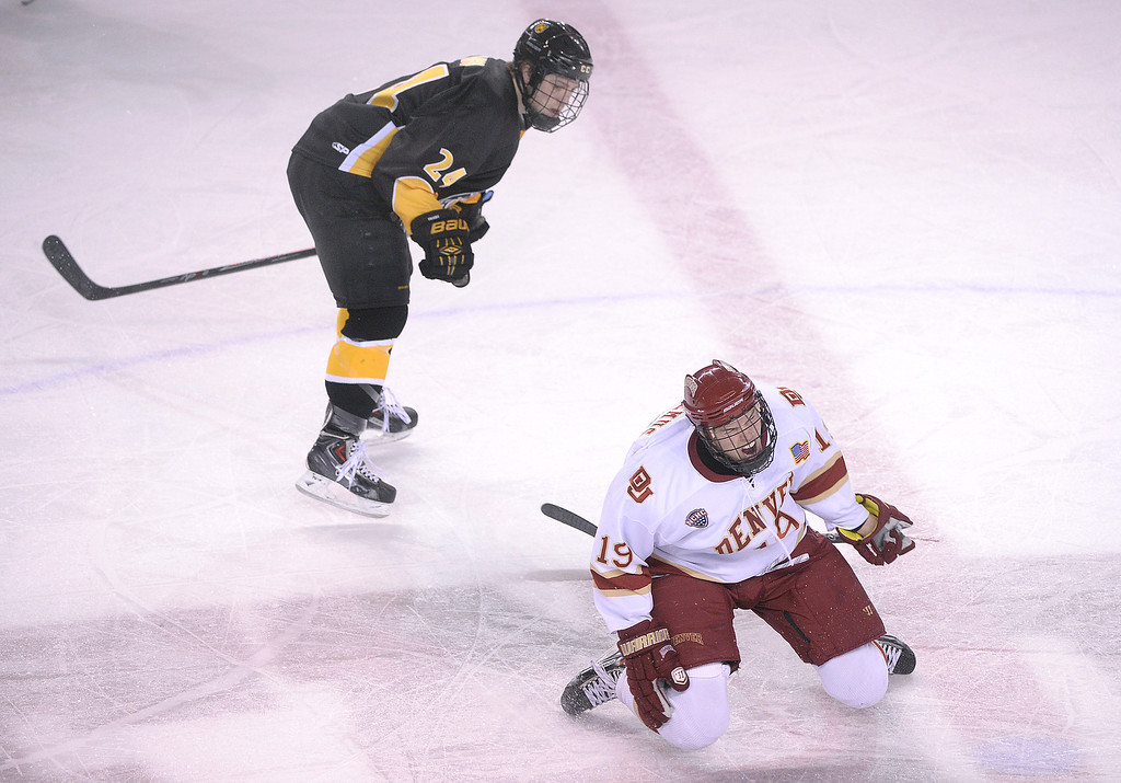 . DENVER, CO. - FEBRUARY 21, 2014: Denver center Daniel Doremus (19) went to the ice in pain after a collision with Tigers\' wing Jared Hanson (24) in the third period. The Colorado College hockey team defeated Denver 3-2 at Magness Arena Friday night, February 21, 2014. Photo By Karl Gehring/The Denver Post