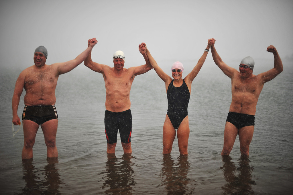 . LITTLETON, CO. - MAY 01 : From left, Craig Lenning of Denver, Jeffrey Hulett of Golden, Jodi Jackson from Hawaii and Cliff Crozier of Lettleton celebrate the opening day of the open water swimming season at Gravel Pond in Chatfield State Park. Littleton, Colorado. May 1, 2013. (Photo By Hyoung Chang/The Denver Post)