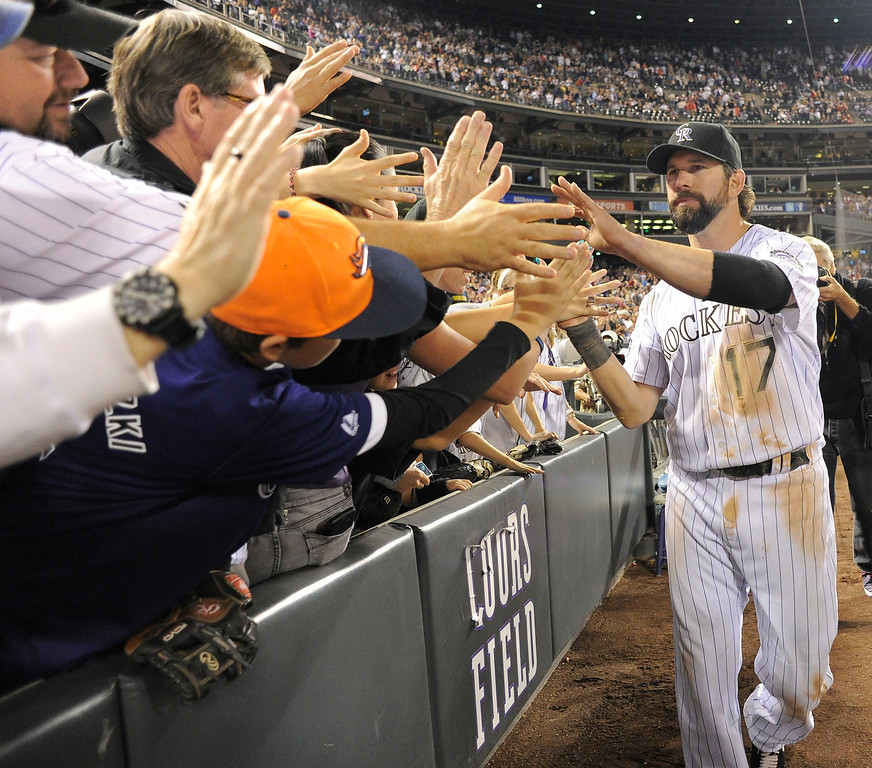 . Todd Helton (17) of the Colorado Rockies high fives the crowd as he enters the dugout after walking off the field at the end of the game against the Boston Red Sox September 25, 2013 at Coors Field. Helton will retire at the end of the season after 17 years with the club. (Photo By John Leyba/The Denver Post)