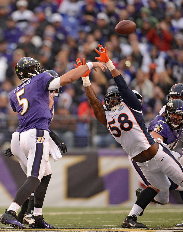 . Baltimore Ravens quarterback Joe Flacco (5) just gets the ball away over the rush by Denver Broncos outside linebacker Von Miller (58) during the third quarter Sunday, December 16, 2012 at M&T Bank Stadium. John Leyba, The Denver Post