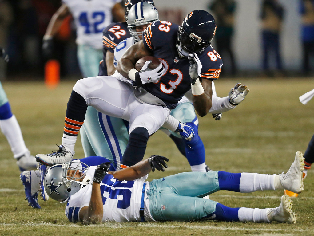 . Chicago Bears tight end Martellus Bennett (83) spins after avoiding a tackle by Dallas Cowboys cornerback Orlando Scandrick (32) during the first half of an NFL football game, Monday, Dec. 9, 2013, in Chicago. (AP Photo/Charles Rex Arbogast)