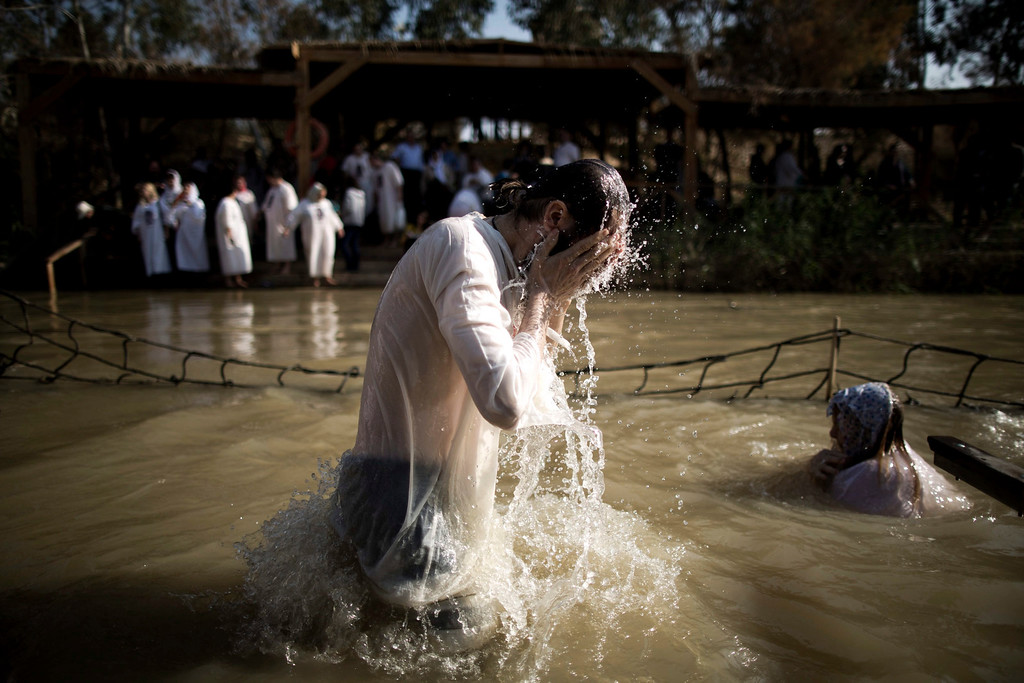 . An Orthodox pilgrim has a dip in the Jordan River for the baptismal ceremony at the site known as Qasr el-Yahud on the West Bank side of the Jordan River near the city of Jericho, 18 January 2014. Thousands of Orthodox pilgrims flocked to the Jordan River to attend the Epiphany feast celebrations at the traditional site where it is believed Jesus was baptized by John the Baptist.  EPA/ABIR SULTAN