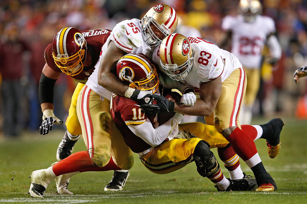 . Washington Redskins quarterback Robert Griffin III is sacked by San Francisco 49ers outside linebacker Ahmad Brooks (55) and tight end Demarcus Dobbs (83) during the second half of an NFL football game in Landover, Md., Monday, Nov. 25, 2013. The 49ers defeated the Redskins 27-6. (AP Photo/Evan Vucci)