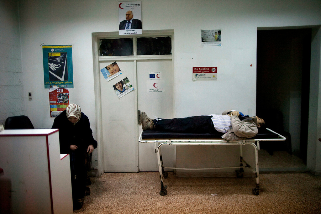 . FILE - The wife of Mohammed Halak slumps in a chair next to his body as she mourns the death of her husband, killed during fighting between Free Syrian Army fighters and the Syrian Army in Idlib, north Syria, Sunday, March 11, 2012. (AP Photo/Rodrigo Abd, File)