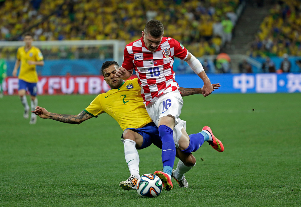 . Brazil\'s Dani Alves, left, challenges Croatia\'s Ante Rebic during the group A World Cup soccer match between Brazil and Croatia, the opening game of the tournament, in the Itaquerao Stadium in Sao Paulo, Brazil, Thursday, June 12, 2014.  (AP Photo/Felipe Dana)