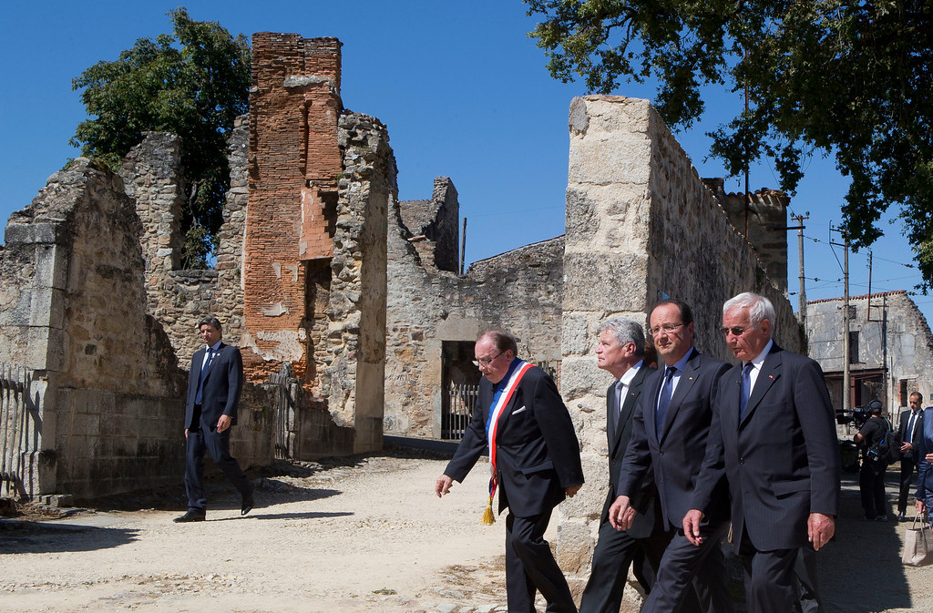 . Foreground from left, Mayor of Oradour-sur-Glane, Raymond Fugier, German President Joachim Gauck, French President Francois Hollande and Robert Hebras, one of the two survivors still alive, walk through the ghost city of Oradour-sur-Glane, southwestern France, Wednesday, Sept. 4, 2013, where on June 10, 1944, the Nazis massacred 642 civilians. Holding hands in quiet tribute, the presidents of Germany and France are visiting the scene of the largest massacre in Nazi-occupied France nearly seven decades ago. Wednesday\'s visit by German President Joachim Gauck to the southwestern French town of Oradour-sur-Glane is the first by a serving German leader. (AP Photo/Michel Euler, Pool)