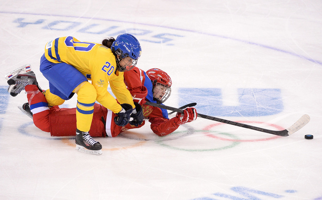 . Russia\'s Alexandra Vafina (R) vies with Sweden\'s Fanny Rask during the Women\'s Ice Hockey Group B match between Sweden and Russia at the Shayba Arena during the Sochi Winter Olympics on February 13, 2014.   ANDREJ ISAKOVIC/AFP/Getty Images