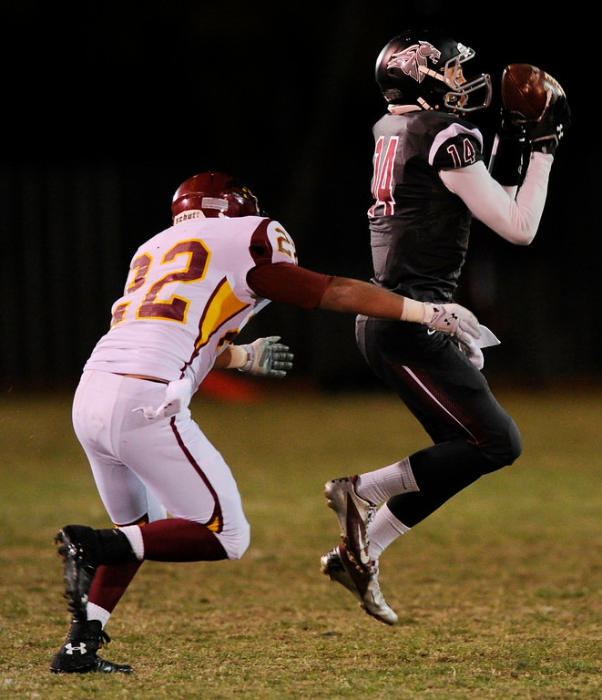 . Rocky Mountain cornerback Trevor Thomas (22) wrapped up Chatfield receiver Brandon Zanier (14) after a catch in the second half.  Photo By Karl Gehring/The Denver Post