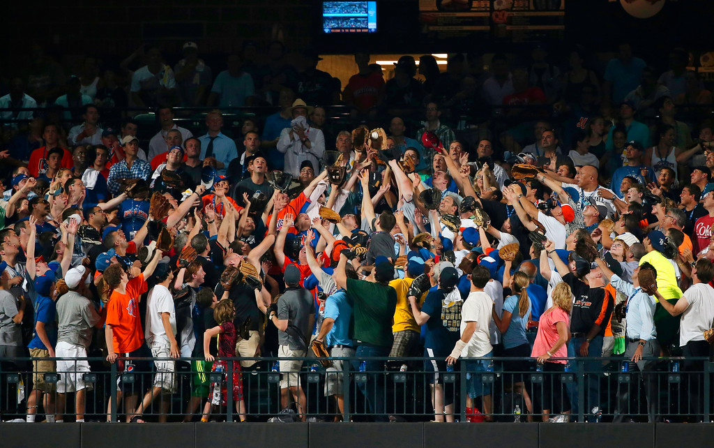 . A fan catches the second home run hit by National League captain David Wright, of the New York Mets, during the MLB All-Star baseball Home Run Derby, on Monday, July 15, 2013 in New York. (AP Photo/Matt Slocum)