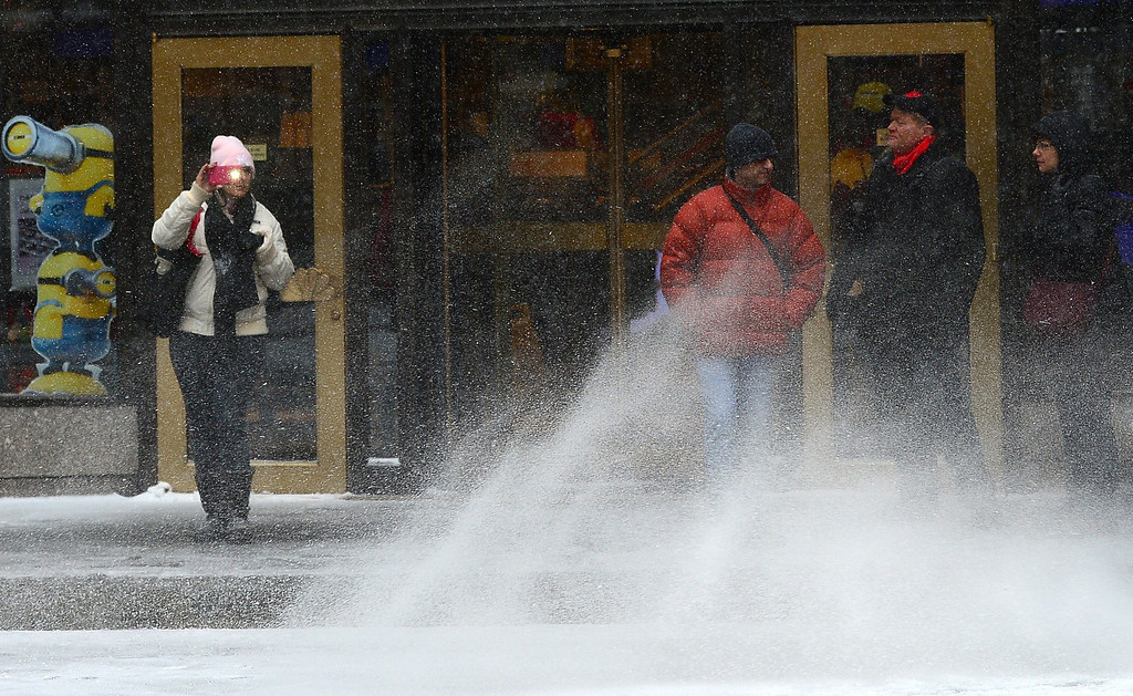 . Pedestrians walk during a snow storm in New York, January 22, 2014. In New York, a storm alert was issued for noon (1700 GMT) Tuesday to 6:00 am (1100 GMT) Wednesday with as much as a foot forecast for the metropolitan region.  AFP PHOTO/Emmanuel DUNAND/AFP/Getty Images