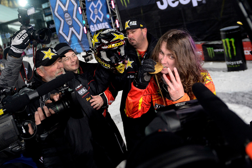 . Colten Moore bites his hardware after capturing the gold medal in the snowmobile freestyle final. Moore\'s older brother, Caleb, died last year as a result of injuries suffered ini the same event. X Games Aspen at Buttermilk on Thursday, January 23, 2014. (Photo by AAron Ontiveroz/The Denver Post)