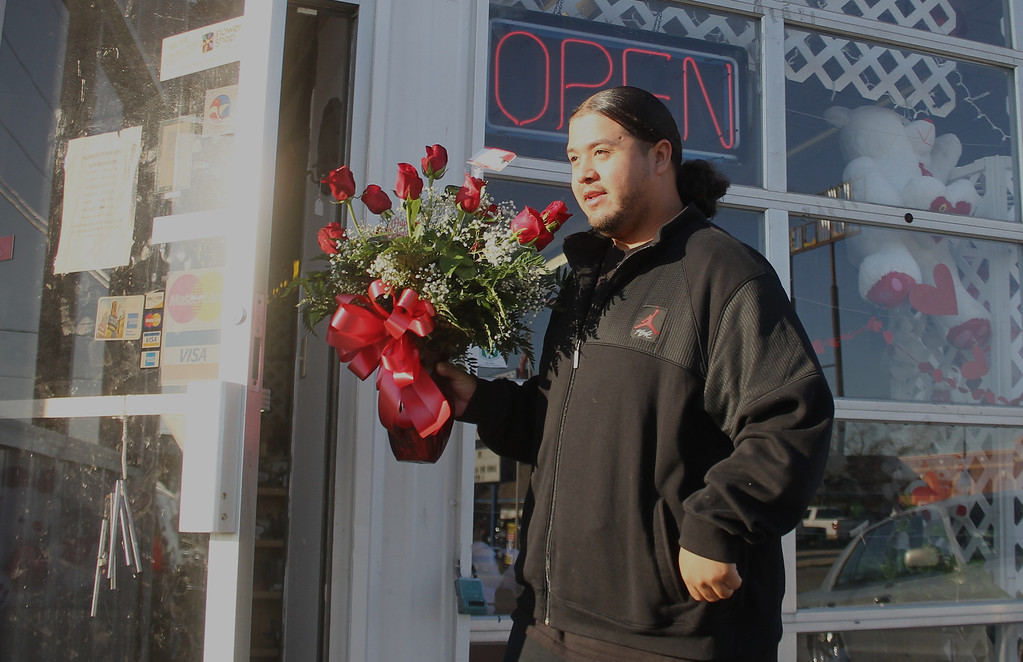 . Edwin Camarillo walks to his car after picking up flowers for Valentine\'s Day at Flowers Texas Style on Thursday, Feb. 14, 2013, in Conroe, Texas. Workers at the shop estimate they will have assembled more than 700 arrangements before the end of Valentine\'s Day. (AP Photo/ The Courier, Jason Fochtman)