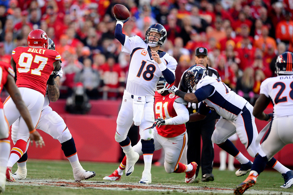 . Peyton Manning (18) of the Denver Broncos throws to Demaryius Thomas (88) on a pass that would be intercepted by Quintin Demps (35) of the Kansas City Chiefs during the first half of action at Arrowhead Stadium.  (Photo by AAron Ontiveroz/The Denver Post)
