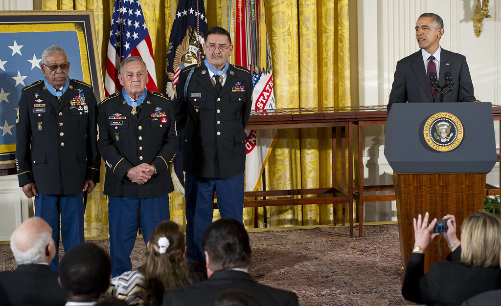 . US President Barack Obama speaks alongside Medal of Honor recipients Staff Sergeant Melvin Morris (L), Sergeant First Class Jose Rodela (C) and Specialist Four Santiago Erevia (R) after they were awarded the Medal of Honor for actions during the Vietnam War, during a ceremony in the East Room of the White House in Washington on March 18, 2014. Obama awarded the Medal of Honor to 24 veterans, 3 of whom are still living, who fought in World War II, the Korean War and the Vietnam War, most of whom were previously denied the prestigious honor due to their Hispanic, black or Jewish backgrounds. The ceremony results from a Pentagon review of Jewish and Hispanic war records ordered by Congress in 2002.    AFP PHOTO / Saul LOEB/AFP/Getty Images