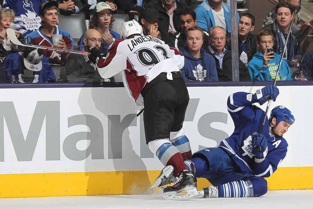 . Gabriel Landeskog #92 of the Colorado Avalanche knocks David Bolland #63 of the Toronto Maple Leafs to the ice during an NHL game at the Air Canada Centre on October 8, 2013 in Toronto, Ontario, Canada. (Photo by Claus Andersen/Getty Images)