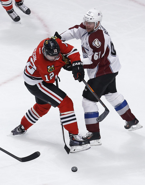 . Colorado Avalanche defenseman Andre Benoit (61) keeps Chicago Blackhawks center Peter Regin (12) from getting a shot on goal during the second period of an NHL hockey game Tuesday, March 4, 2014, in Chicago. (AP Photo/Charles Rex Arbogast)