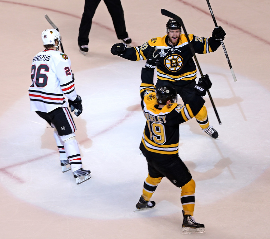 . Rich Peverley #49 of the Boston Bruins celebrates with Daniel Paille #20 after scoring a goal as Michal Handzus #26 of the Chicago Blackhawks looks on during the first period in Game Four of the 2013 NHL Stanley Cup Final at TD Garden on June 19, 2013 in Boston, Massachusetts.  (Photo by Bruce Bennett/Getty Images)