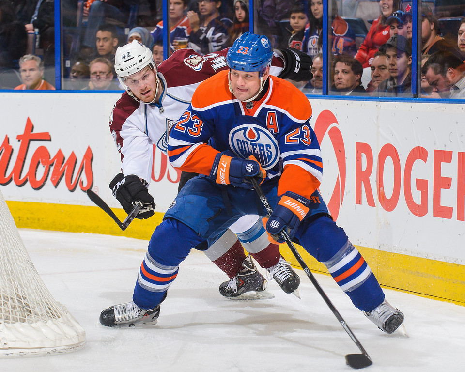 . Matt Hendricks #23 of the Edmonton Oilers skates with the puck against Brad Malone #42 of the Colorado Avalanche during an NHL game at Rexall Place on April 8, 2014 in Edmonton, Alberta, Canada. (Photo by Derek Leung/Getty Images)