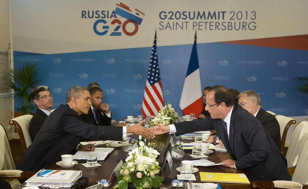 . US President Barack Obama, left, and French President Francois Hollande, right, reach across the table to shake hands during their bilateral meeting at the G-20 Summit, Friday, Sept. 6, 2013 in St. Petersburg, Russia. (AP Photo/Pablo Martinez Monsivais)