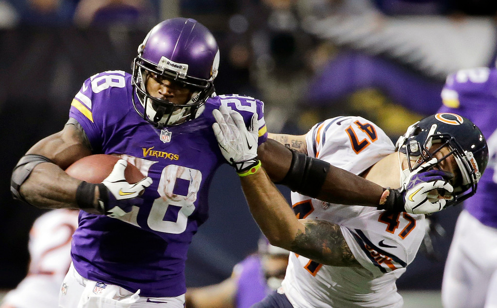 . Minnesota Vikings running back Adrian Peterson, left, tries to break a tackle from Chicago Bears free safety Chris Conte during the fourth quarter of an NFL football game on Sunday, Dec. 1, 2013, in Minneapolis. The Vikings won 23-20 in overtime. (AP Photo/Ann Heisenfelt)