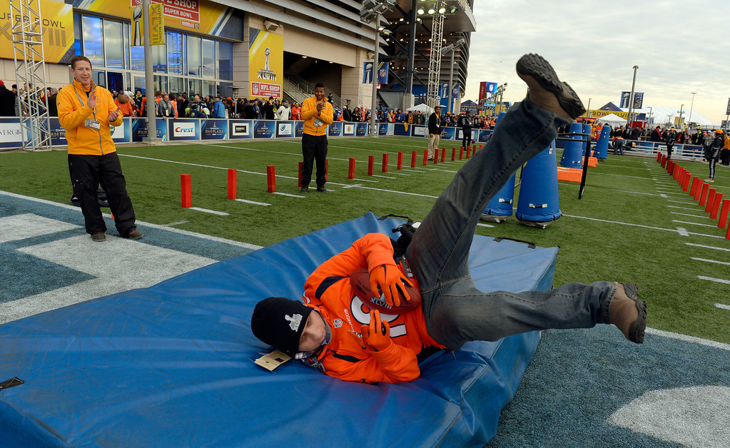 . Dave Browne of Belleville, NJ scores a touchdown while playing a game for the fans outside of the stadium prior to the start of the game.  The Denver Broncos vs the Seattle Seahawks in Super Bowl XLVIII at MetLife Stadium in East Rutherford, New Jersey Sunday, February 2, 2014. (Photo by Craig Walker/The Denver Post)