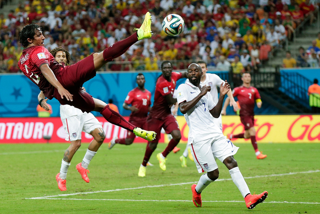 . Portugal\'s Bruno Alves kicks the ball above United States\' DaMarcus Beasley, lower right, during the group G World Cup soccer match between the United States and Portugal at the Arena da Amazonia in Manaus, Brazil, Sunday, June 22, 2014. (AP Photo/Marcio Jose Sanchez)