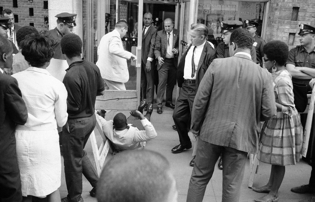 . Herb Callender, center foreground, an official of CORE (Congress of Racial Equality) hits the sidewalk in front of the U.S. Mission to the United Nations in New York, July 22, 1966, after he was thrown out of the building during attempt to stage a sit-in.  The incident climaxed demonstration of pickets protesting U.S. relations with South Africa. (AP Photo/John Rooney)