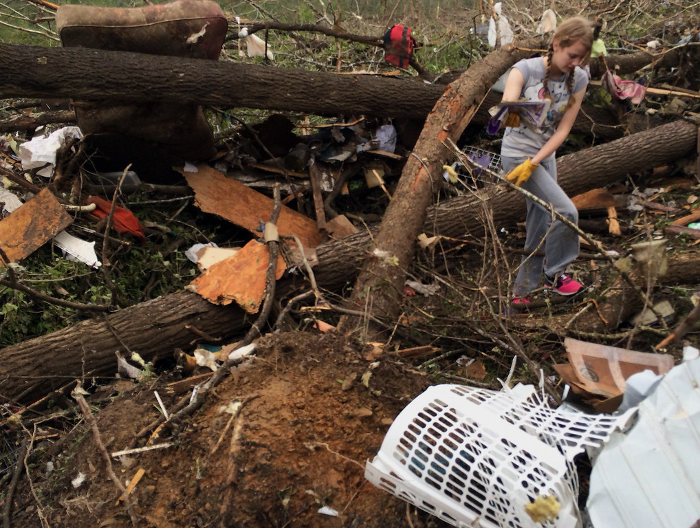 . In this Monday, April 28, 2014, photo taken with a cell phone, Emily Tittle picks through rubble after a tornado stuck Sunday, in Paron, Ark. Tittle said she, her eight siblings and her parents went for safety under the stairs in the two-story house, but only half of them made it before the walls were obliterated by the twister that left just the foundation behind. Her father, Rob Tittle, and two sisters, Tori, 20, and Rebekah, 14, were killed in the storm. (AP Photo/Christina Huynh)