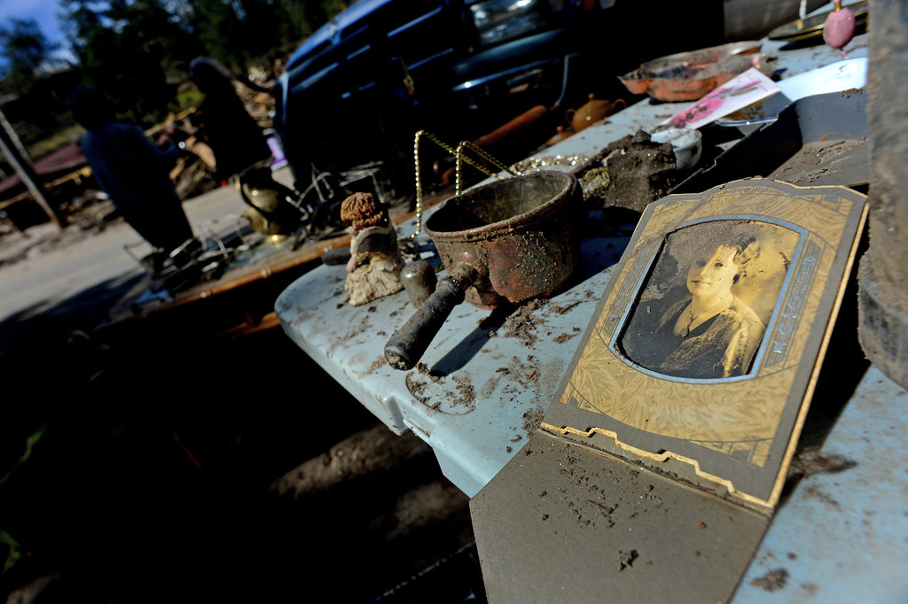 . GLEN HAVEN, CO - OCTOBER 8: Glen Haven Inn owner Sheila Sellers, in back, looks at what remains of some of the thousands of antiques that filled the inside of her historic Glen Haven Inn in Glen Haven, CO on October 8, 2013.  The Inn was one of the only businesses that actually made it in the town but has been inundated with mud and debris.  (Photo By Helen H. Richardson/ The Denver Post)