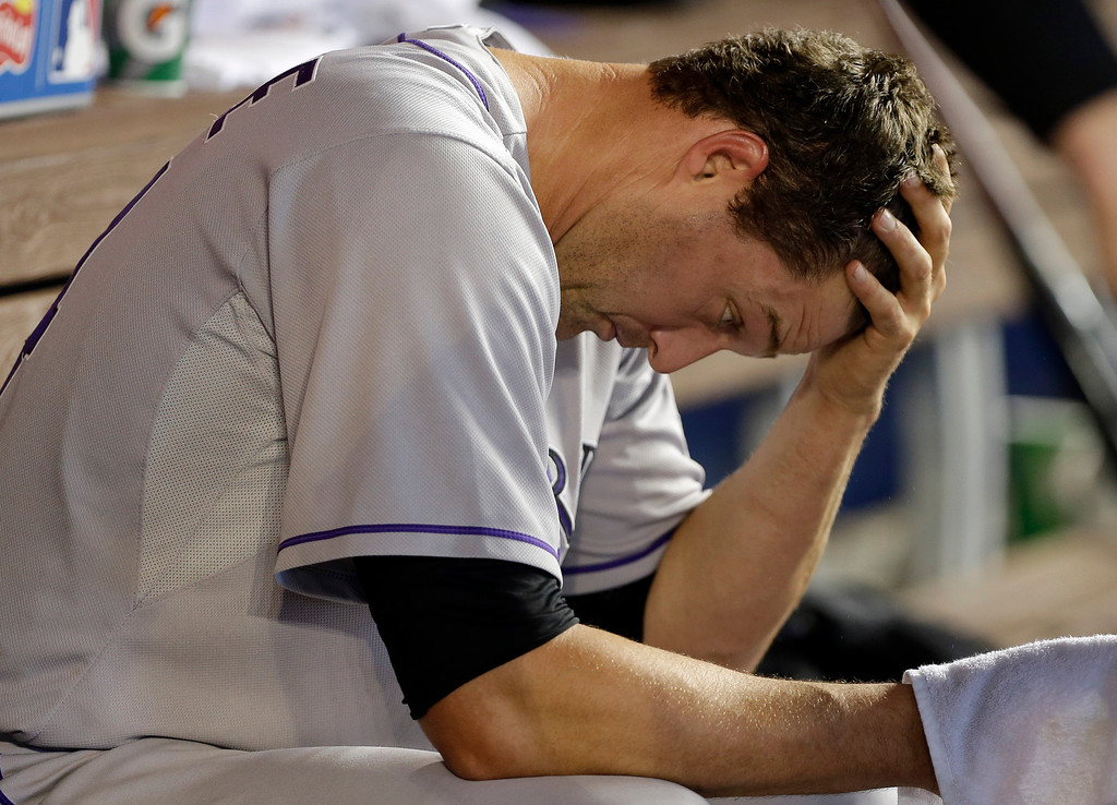 . Colorado Rockies relief pitcher Matt Belisle sits in the dugout after pitching in the eighth inning when the Miami Marlins scored four runs during a baseball game, Thursday, April 3, 2014, in Miami. The Marlins defeated the Rockies 8-5. (AP Photo/Lynne Sladky)