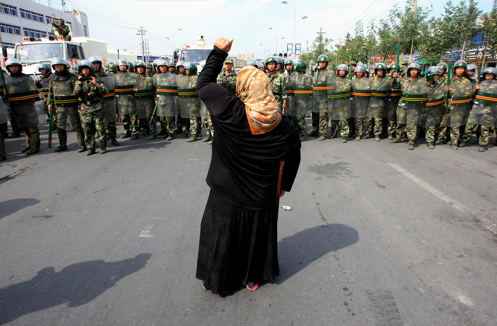 . A local woman on a crutch shouts at Chinese paramilitary police wearing riot gear as a crowd of angry locals confront security forces on a street in the city of Urumqi in China\'s Xinjiang Autonomous Region July 7, 2009.REUTERS/David Gray