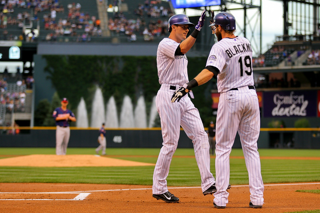 . DENVER, CO - JULY 11:  Drew Stubbs #13 of the Colorado Rockies is congratulated by Charlie Blackmon #19 after hitting a two run home run during the first inning off of Kris Johnson #53 of the Minnesota Twins at Coors Field on July 11, 2014 in Denver, Colorado.  (Photo by Justin Edmonds/Getty Images)