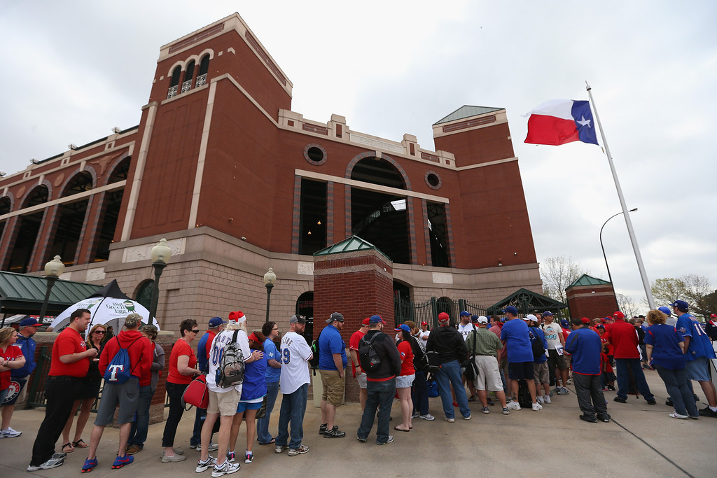 . Fans enter the gates before the MLB Opening Day game between the Philadelphia Phillies and the Texas Rangers at Globe Life Park in Arlington on March 31, 2014 in Arlington, Texas.  (Photo by Ronald Martinez/Getty Images)