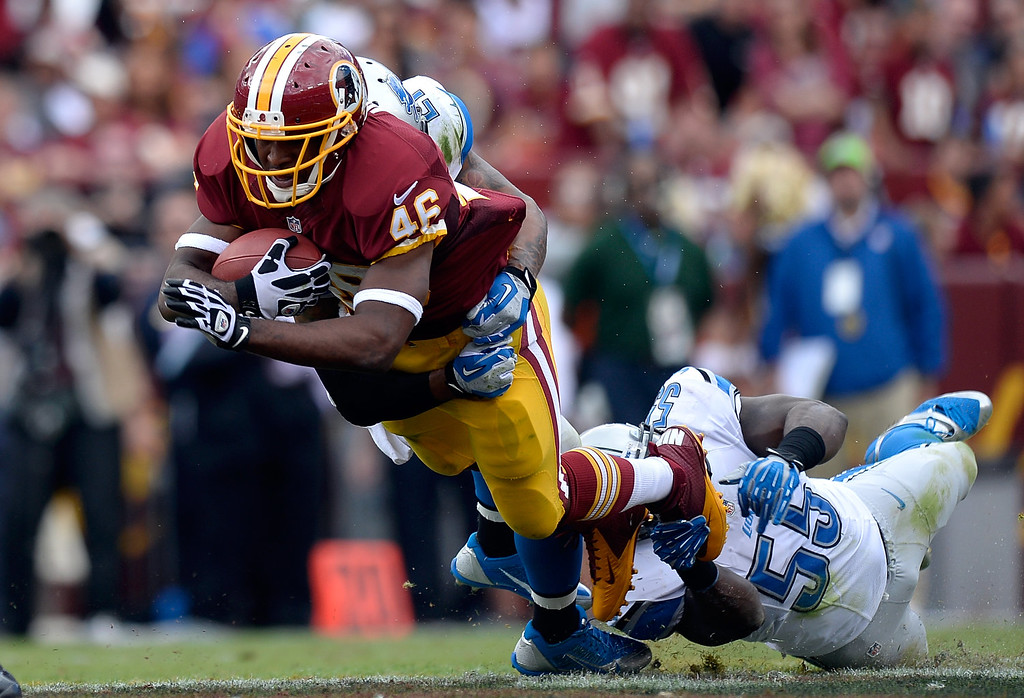 . LANDOVER, MD - SEPTEMBER 22:  Alfred Morris #46 of the Washington Redskins is tackeld by Stephen Tulloch #55 of the Detroit Lions in the second quarter during a game at FedExField on September 22, 2013 in Landover, Maryland.  (Photo by Patrick McDermott/Getty Images)