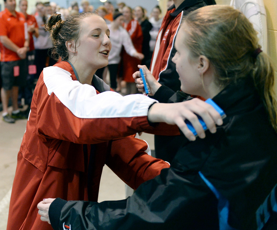 . THORNTON, CO. - FEBRUARY 15, 2014: Regis sophomore diver McKensi Austin, left, congratulated one of her competitors on the podium following her win Saturday. The CHSAA 5A Girl\'s State Swimming Championships wrapped up Saturday night February 14, 2104.  Photo By Karl Gehring/The Denver Post