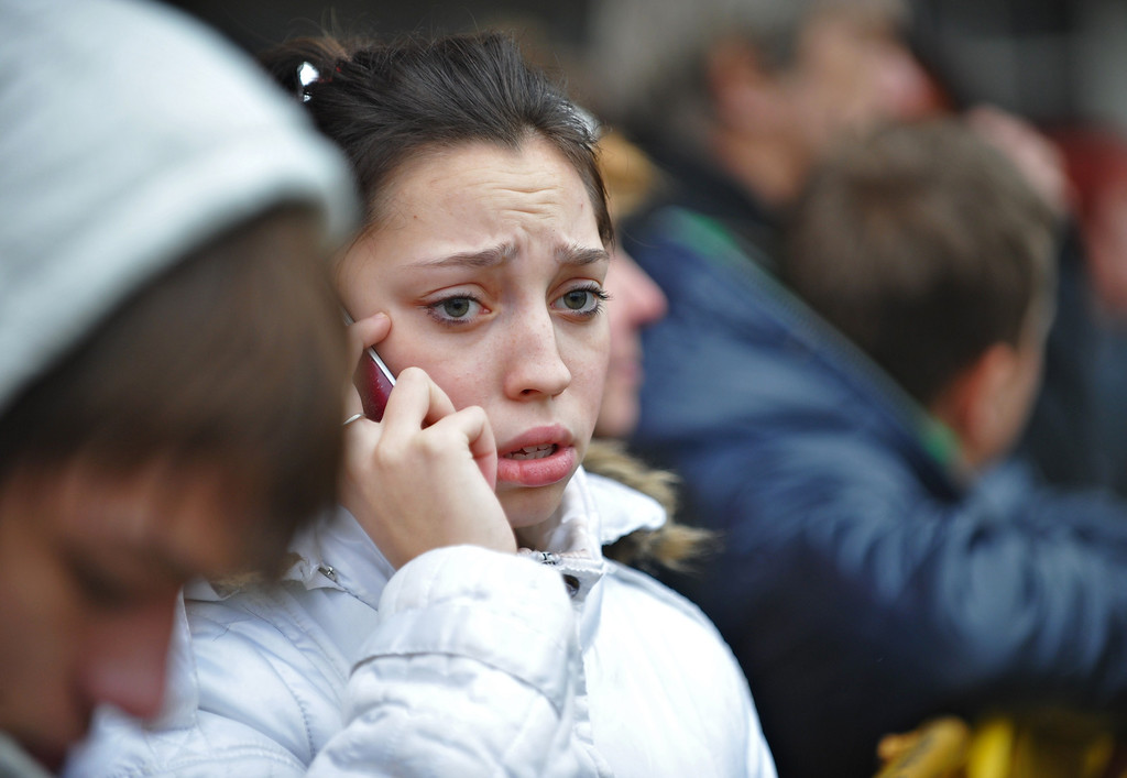 . A woman speaks on the phone as she waits foe news at the scene where the Maxima supermarket roof collapsed in Riga on November 22, 2013.  AFP PHOTO/ILMARS ZNOTINS/AFP/Getty Images